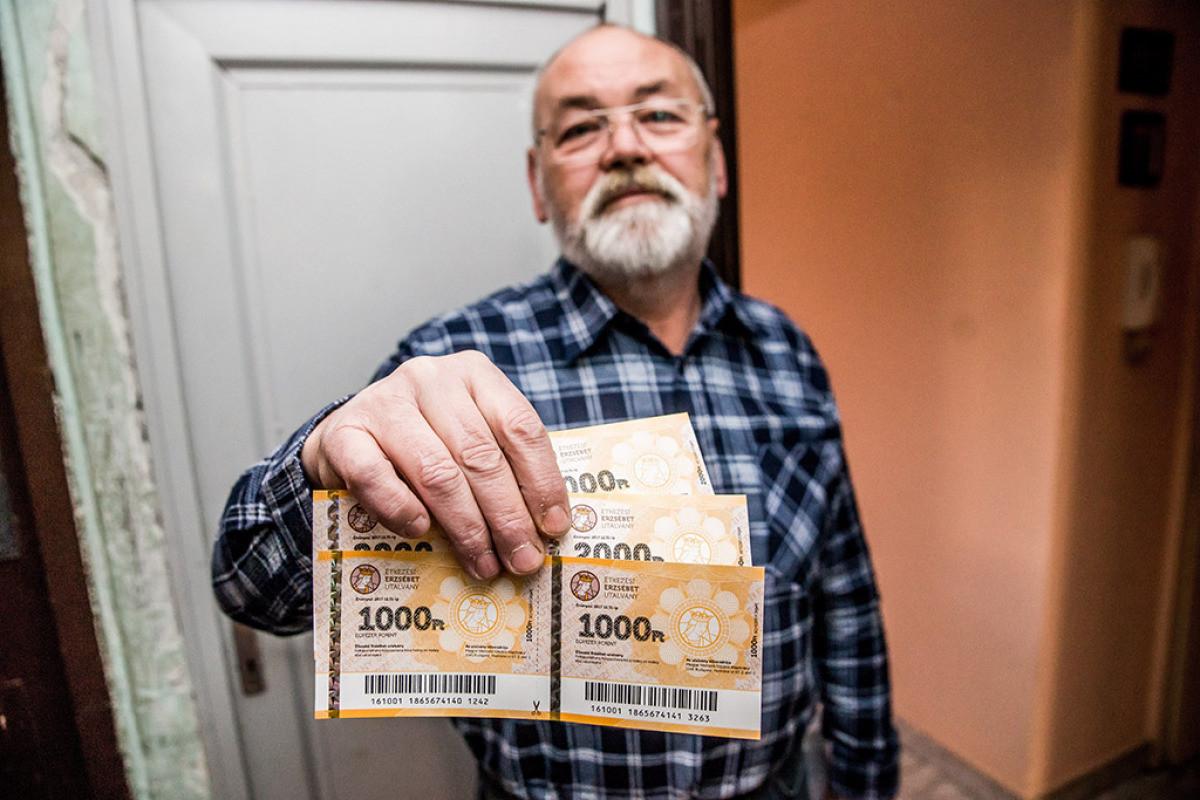 Egy nyugdíjas mutatja a Magyar Posta Zrt. munkatársa által kézbesített Erzsébet-utalványokat Budapesten 2016. december 13-án.