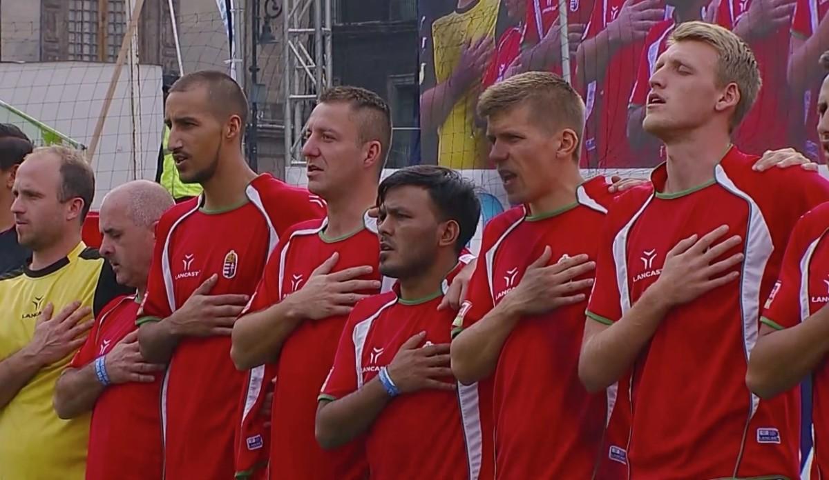 A magyar hajléktalanok futballválogatottja énekli a himnuszt a Magyarország-Portugália mérkőzés előtt.