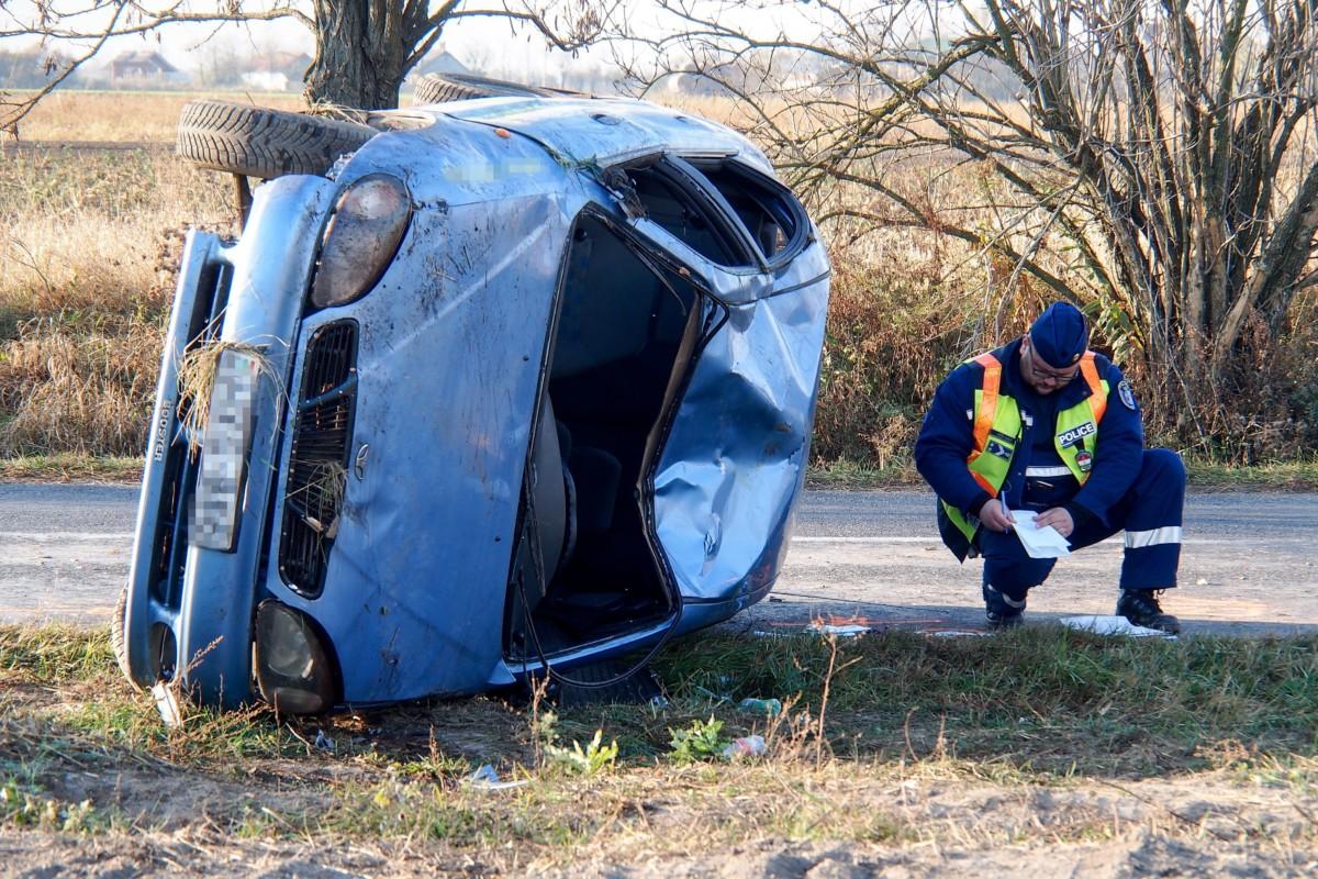 Rendőr helyszínel egy felborult autó mellett Kunszentmiklóson 2018. november 8-án. A jármű a kanyarban borult fel, vezetője az autó alá szorult és életét vesztette. A kocsi másik utasa könnyebben megsérült.