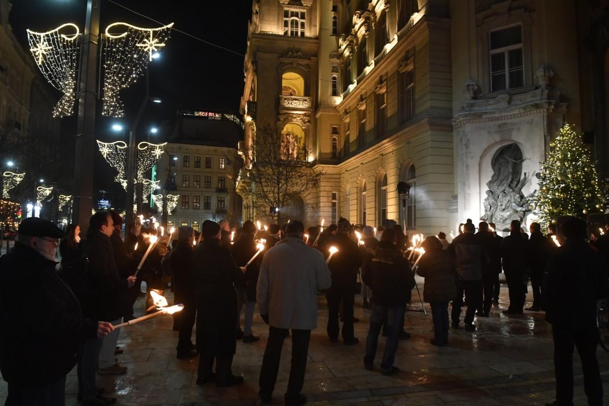 """A Fidelitas """"Fáklyagyújtás az üldözött keresztényekért"""" elnevezésű megemlékezése az Egyetem téri Kisboldogasszony-templom falánál lévő hősi emlékműnél 2018. december 17-én."""