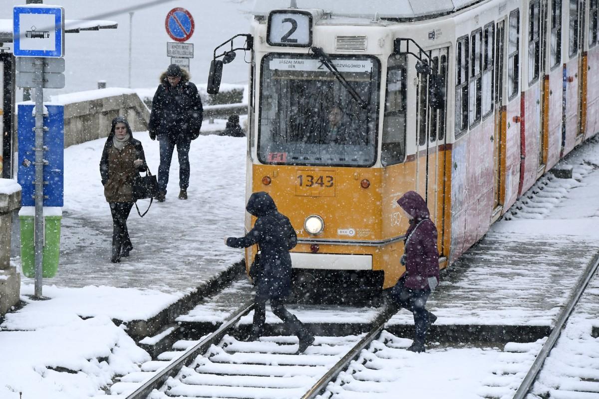 Utasok a 2-es villamosnál Budapesten, a behavazott Széchenyi téri megállóban 2018. december 15-én.
