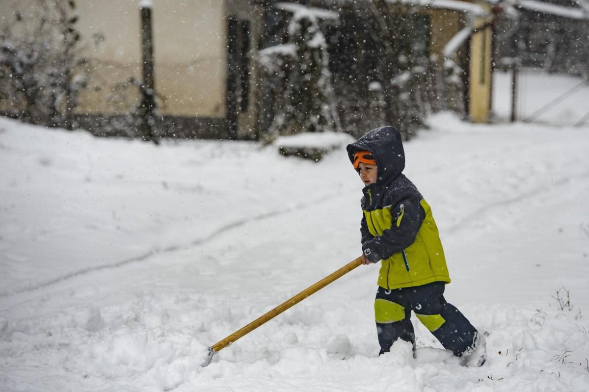 Havat lapátol egy kisfiú Salgótarjánban 2018. december 15-én.
