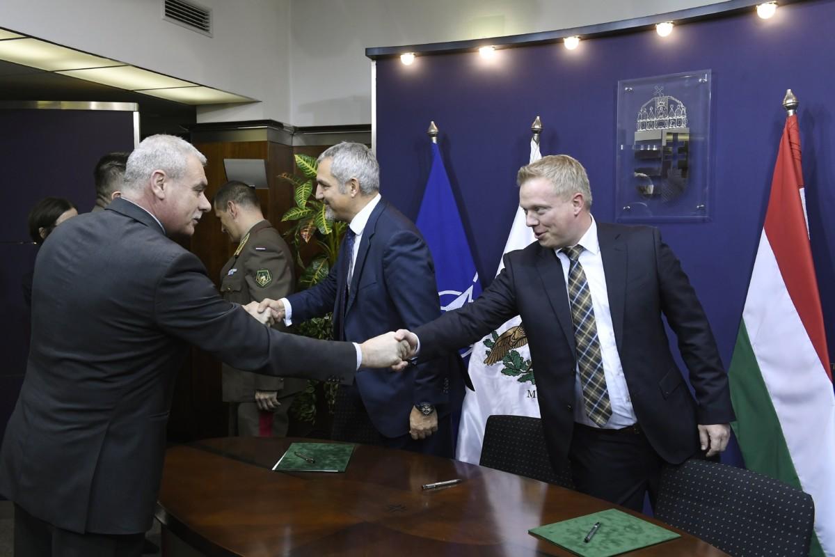 Szabó István honvédelmi államtitkár (b) és Dennis Bernitz, az Airbus Helicopters értékesítési vezetője kezet fog a tizenhat Airbus H225M típusú helikopter beszerzésről szóló szerződés aláírása után Budapesten, a Honvédelmi Minisztériumban 2018. december 14-én. Középen Thomas Hein, a cég kereskedelmi vezetője.