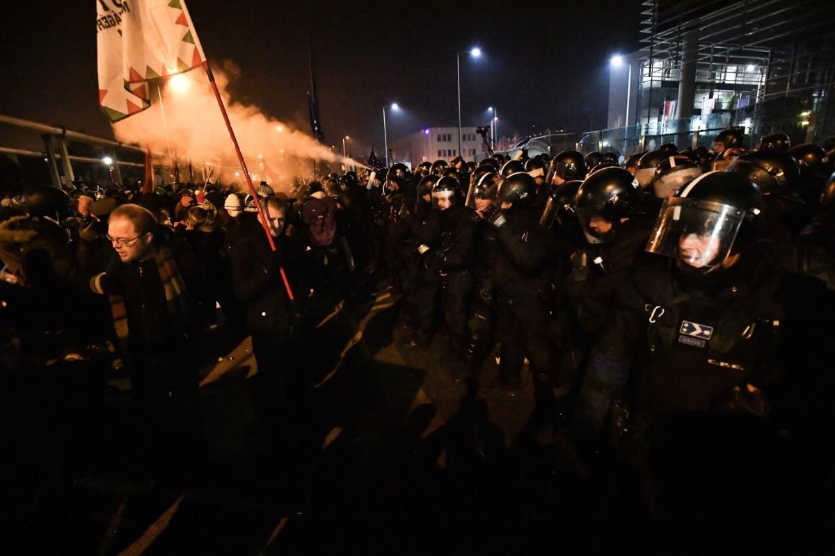 """A """"Boldog karácsonyt, miniszterelnök úr!"""" címmel meghirdetett kormányellenes demonstráció résztvevői a rendőrsorfallal szemben az MTVA Kunigunda utcai székházánál 2018. december 16-án."""