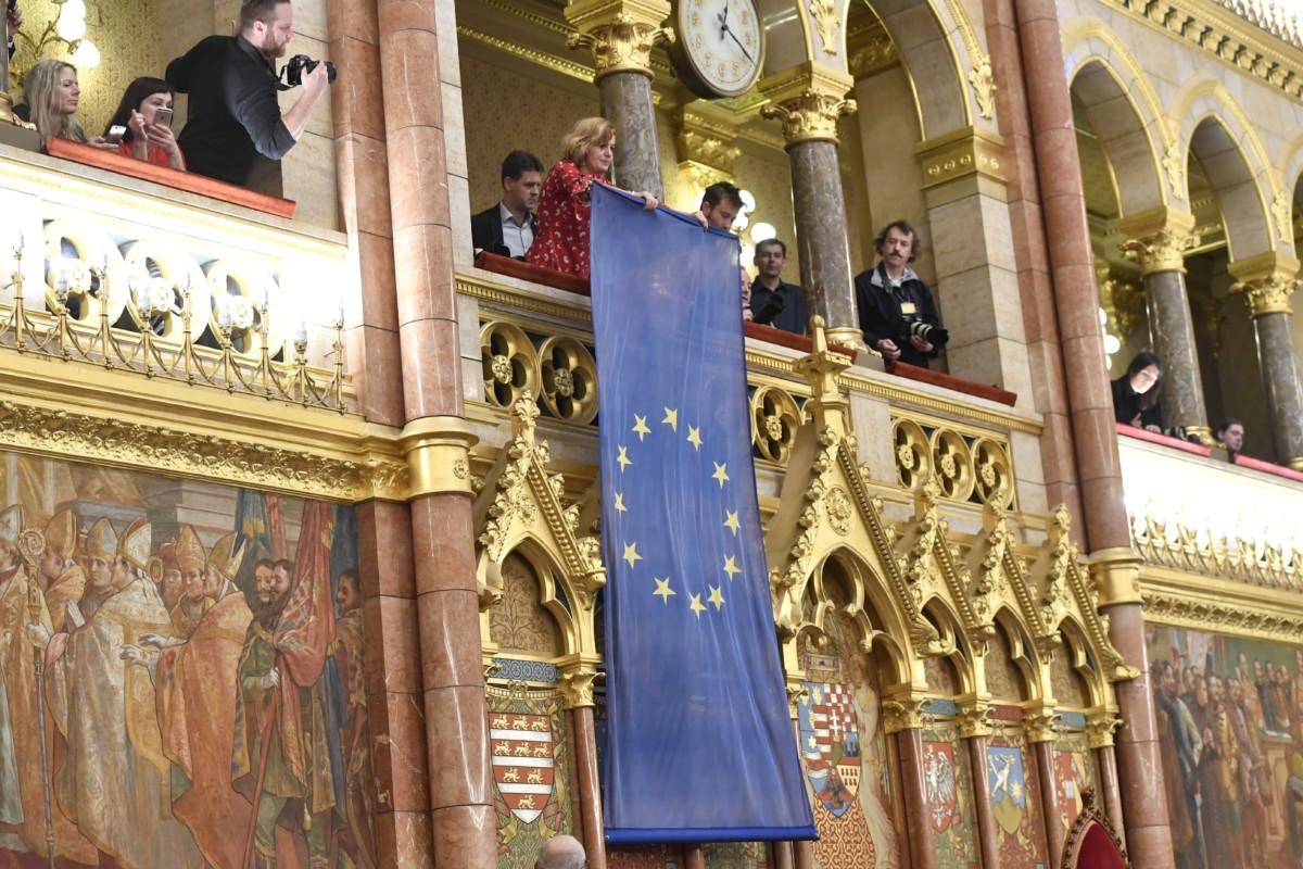 Bangóné Borbély Ildikó uniós zászlót lógat le egy karzatról Országgyűlés a plenáris ülésén 2018. december 12-én.