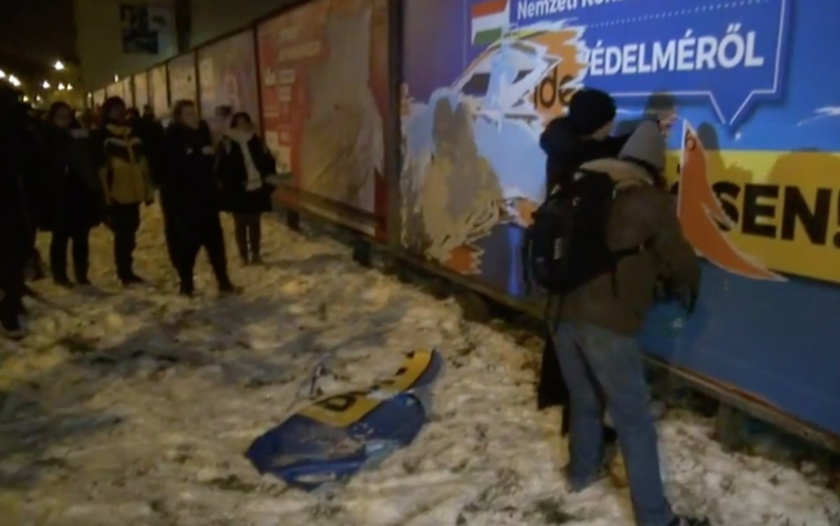 Konzultációs plakátokat tépkednek a tüntetők, a tömeg ujjong, a rendőrök nem annyira