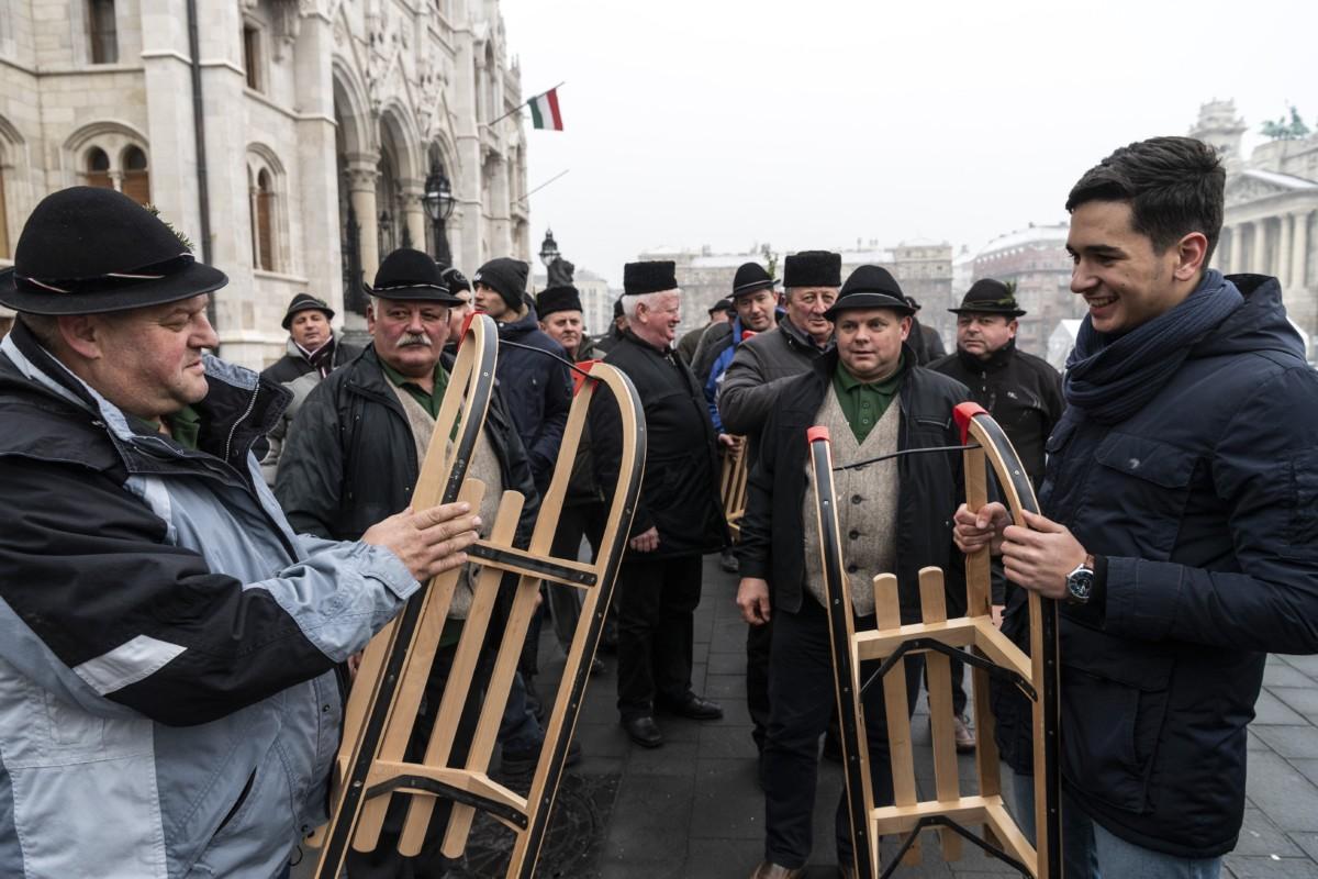 A Gyimes Völgye Férfikórus tagjai az Ország Karácsonyfájánál a Kossuth téren 2018. december 21-én. A kórus tagjai tíz szánkót hoztak, hogy részben pótolják a december közepén tartott tüntetésen ellopott, megrongált - rászoruló gyermekeknek szánt - sporteszközöket. Az Ország Karácsonyfája körül - immár hagyományosan - 120 szánkóból álló kerítést állítottak fel.