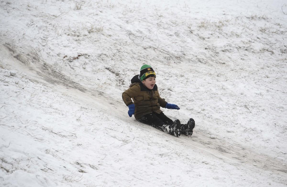 Kisfiú csúszik a hóban a városligeti Királydombon 2019. január 9-én.