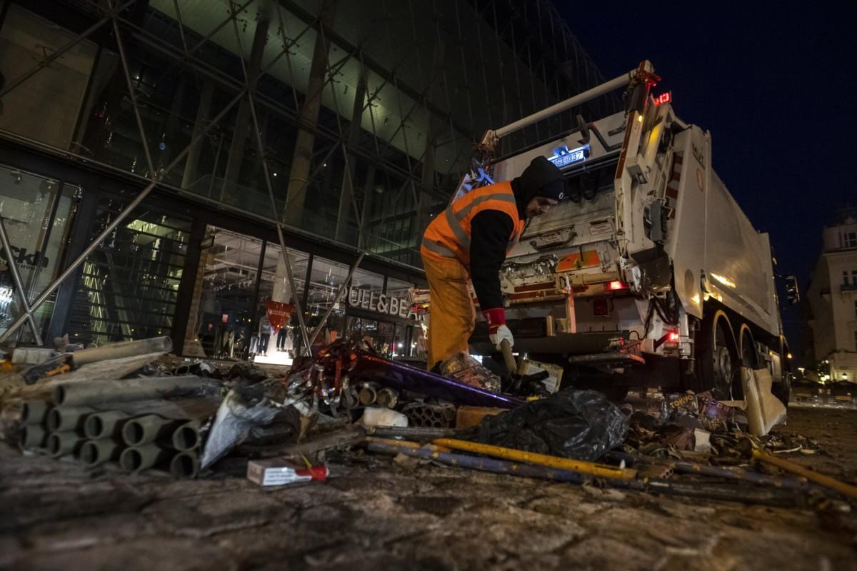 A Fővárosi Közterület-fenntartó Zrt. dolgozói takarítanak a szilveszteri ünneplés után a belvárosi Vörösmarty téren 2019. január 1-jére virradóan.