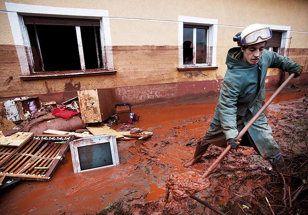 Egy férfi vöröiszapot lapátol Devecseren. A MAL Zrt. Ajka melletti tározójából 2010. október 4-én mintegy egymillió köbméternyi mérgező, maró hatású vörösiszap ömlött ki gátszakadás miatt. A katasztrófa három települést - Devecser, Kolontár, Somlóvásárhely – érint, közel 40 négyzetkilométeres terület lakossága és élővilága van veszélyben.