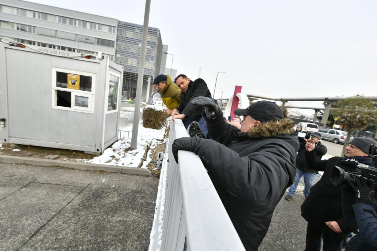 Korózs Lajos (elöl) és Molnár Zsolt MSZP-s országgyűlési képviselők átmásznak a kerítésen az MTVA Kunigunda utcai székházának területére 2018. december 17-én.