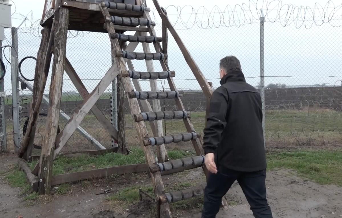 """Orbán Viktor miniszterelnök felmászik egy határőr-bódéba a szerb-magyar határon Tompánál 2018. március 16-án. A tákolmányról azt mondta, """"ez egy komoly építmény, a világ bármely országa megirigyelhetné""""."""