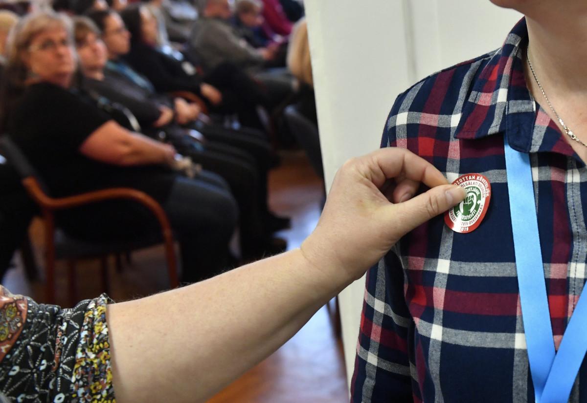 Matricát helyez egy dolgozó munkatársa ruhájára a Magyar Köztisztviselők, Közalkalmazottak és Közszolgálati Dolgozók Szakszervezete (MKKSZ) egynapos sztrájkjának elindításán tartott gyűlésen a XV. kerületi polgármesteri hivatalban 2019. március 14-én.