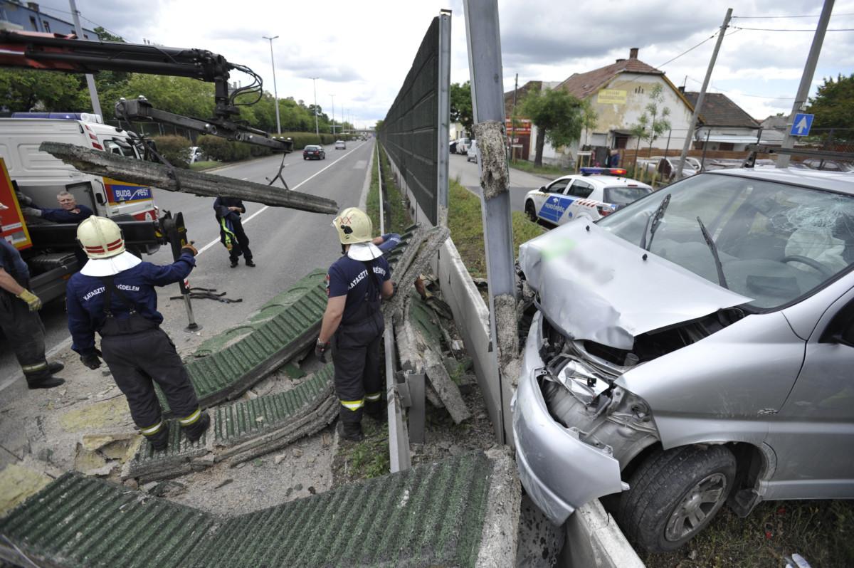 Tűzoltók a XX. kerületben, a Nagykőrösi út és a Kossuth Lajos utca kereszteződésénél, ahol több méteres szakaszon kidöntötte egy autós a zajvédő falat 2019. május 10-én.