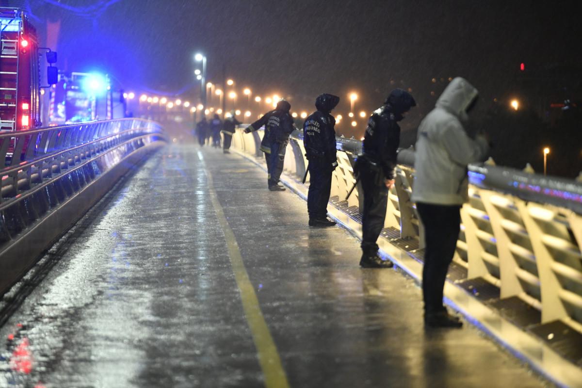 Tűzoltók és rendőrök figyelik a Dunát a Lágymányosi hídról a Parlament közelében ütközés miatt felborult és elsüllyedt Hableány rendezvényhajó utasai után kutatva 2019. május 29-én.