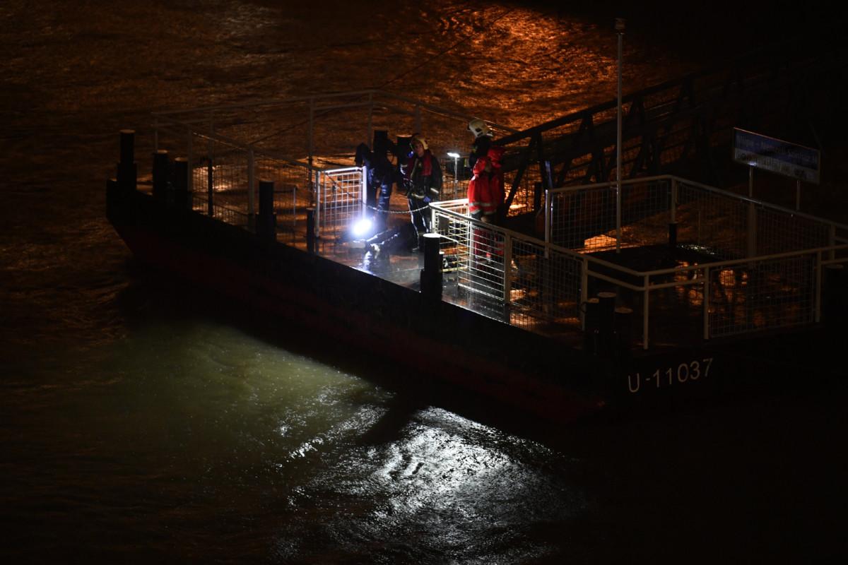 Tűzoltó és rendőr figyeli a Dunát a Müpa előtti pontonról a Parlament közelében ütközés miatt felborult és elsüllyedt Hableány rendezvényhajó utasai után kutatva 2019. május 29-én.
