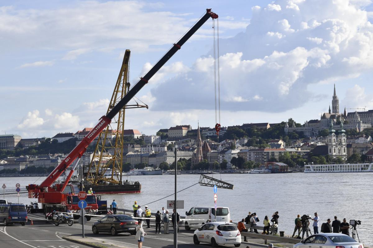 A Margit hídnál hajóbalesetben elsüllyedt Hableány turistahajó mentését segítő eszközt rakják le daruval a rakparton, az úszódaru közelében 2019. május 31-én.