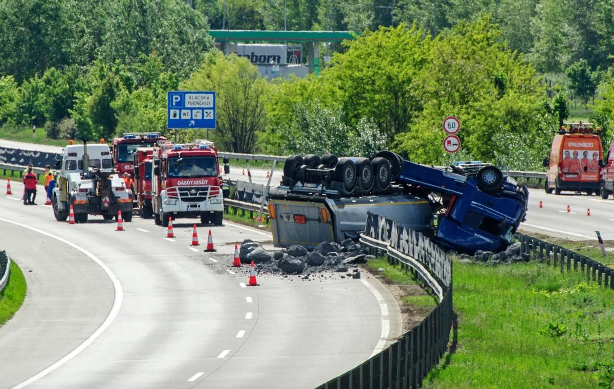 Tűzoltók dolgoznak egy veszélyes anyagot szállító, felborult kamion mentésén az M0-s autóúton Vecsésnél 2019. május 10-én.