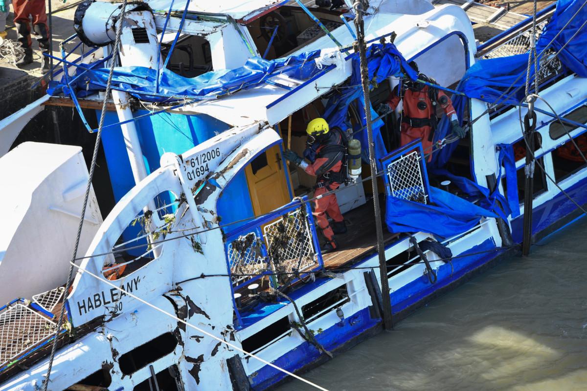 Búvárok a kiemelést követően a víz felszíne felett, holtestek után kutatva átvizsgálják a balesetben elsüllyedt Hableány turistahajó roncsát a Margit hídnál 2019. június 11-én.