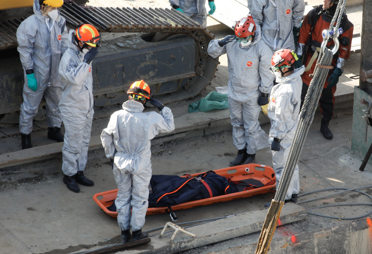 A mentőalakulat tagjai tisztelegnek a balesetben elsüllyedt Hableány turistahajó roncsából kiemelt holttest mellett a Margit hídnál horgonyzó uszályon 2019. június 11-én.