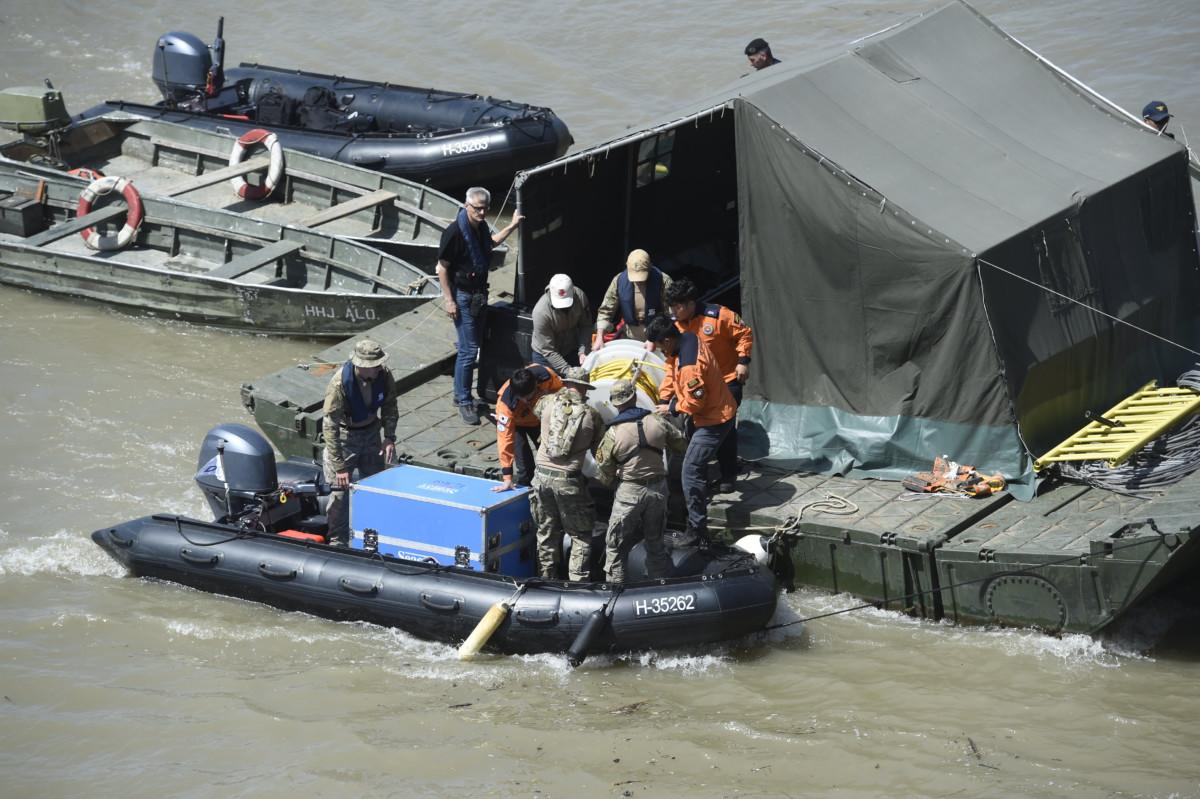 A dél-koreai és a magyar mentőegység tagjai felszerelést pakolnak ki a kiépített keresőpontonra a hajóbalesetben elsüllyedt Hableány turistahajó közelében 2019. június 1-jén.