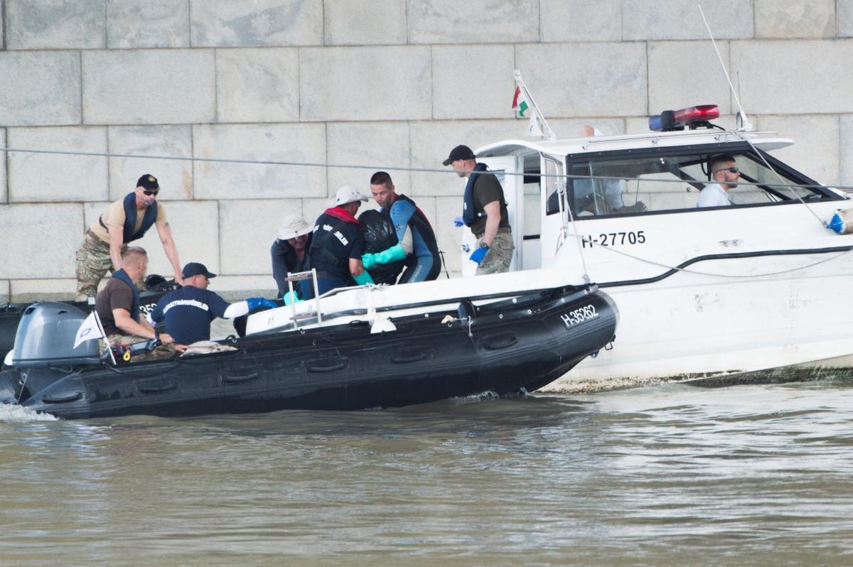 A hajóroncsból felhozott holttestet emelik át egy rendőrségi motorcsónakba a kutatási munkálatokat végző szakemberek a balesetben elsüllyedt Hableány turistahajó közelében, a Margit hídnál 2019. június 5-én.