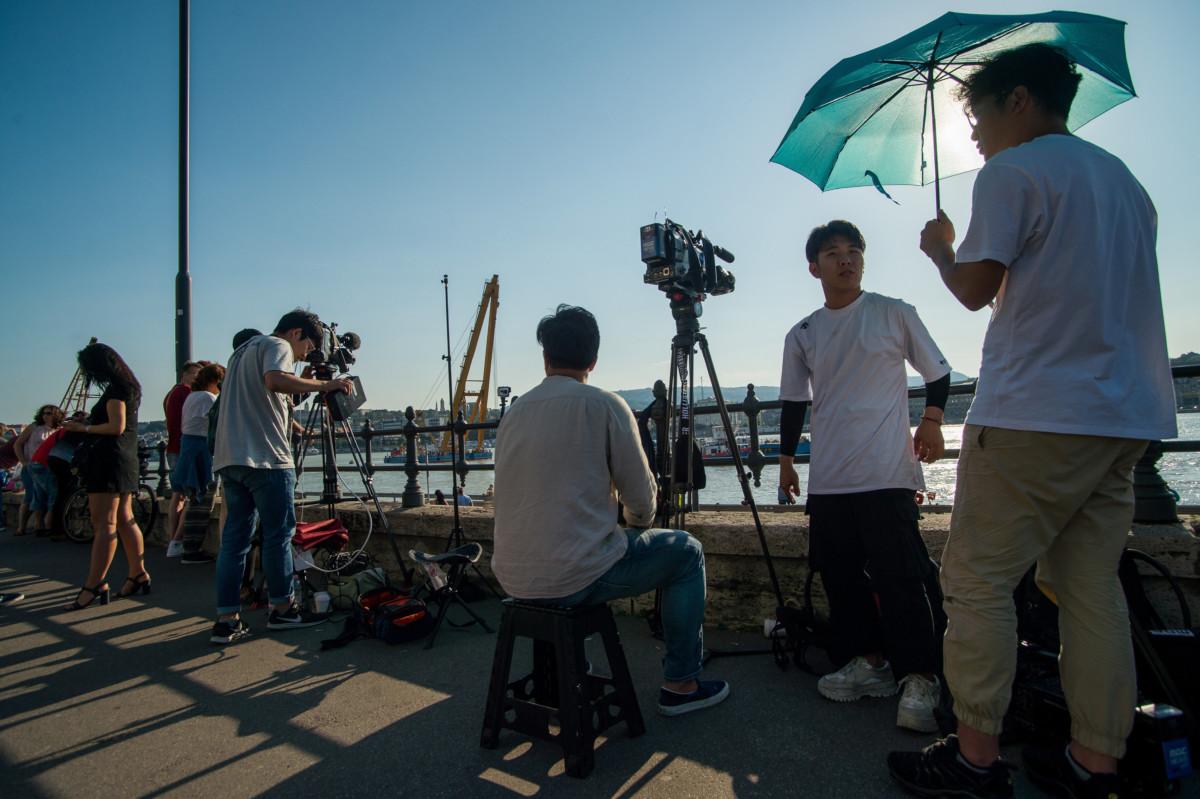 Koreai televíziós stáb dolgozik a hajóbalesetben elsüllyedt Hableány turistahajó közelében a Margit hídnál 2019. június 7-én.