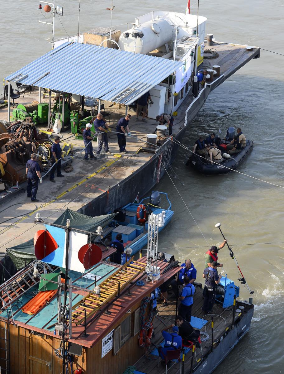 A roncs kiemelését előkészítő szakemberek a balesetben elsüllyedt Hableány turistahajó közelében, a Margit hídnál horgonyzó uszályon 2019. június 10-én.