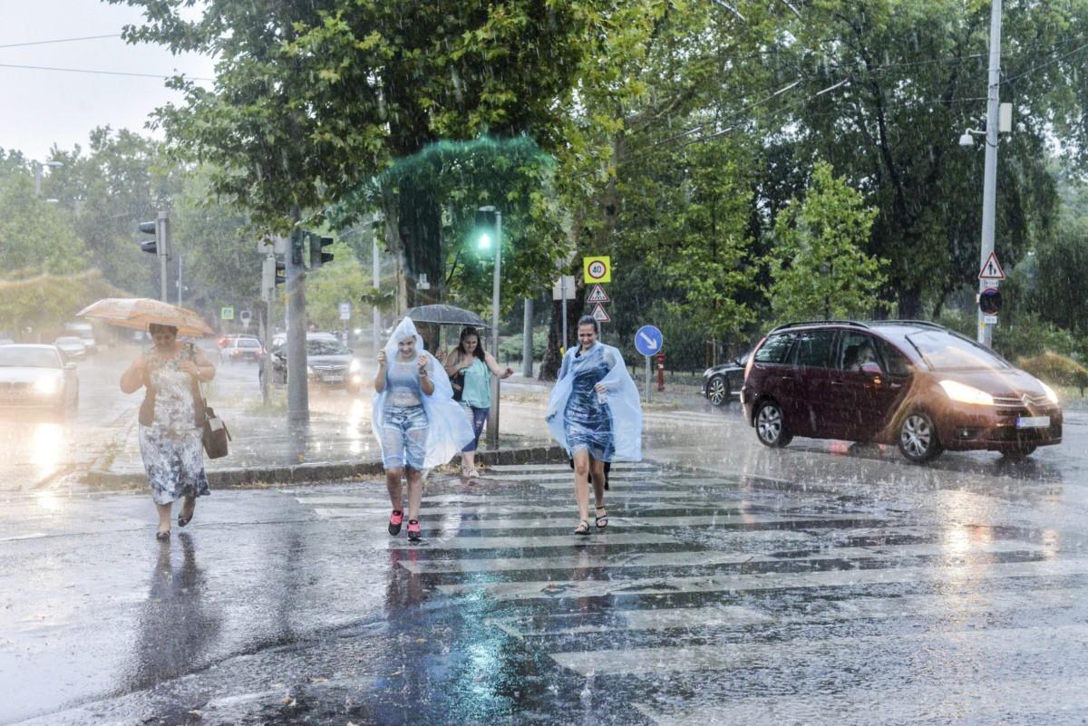 Gyalogosok futnak át az úttesten az esőben Budapesten, az Állatkerti sétányon 2017. augusztus 6-án.