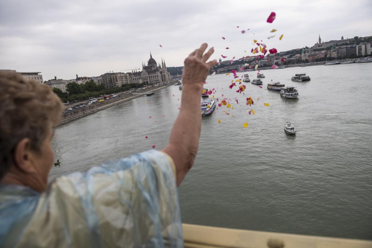 Virágszirmokat szór a Dunába egy megemlékező a dunai hajóbaleset két magyar áldozatának, a Hableány kapitányának és matrózának búcsúztatásán a Margit hídon 2019. július 12-én.