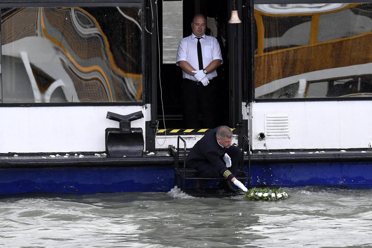 Koszorút engednek a Dunába a koreai áldozatok emlékére a dunai hajóbaleset két magyar áldozatának, a Hableány kapitányának és matrózának búcsúztatásán a Margit hídnál 2019. július 12-én.