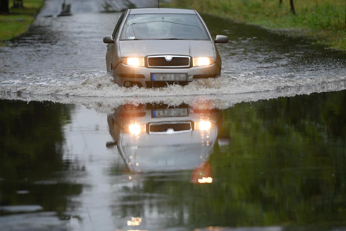 A hirtelen lezúduló eső miatt összegyűlt vízben halad egy jármű a debreceni Benczúr Gyula utcában 2019. július 27-én.