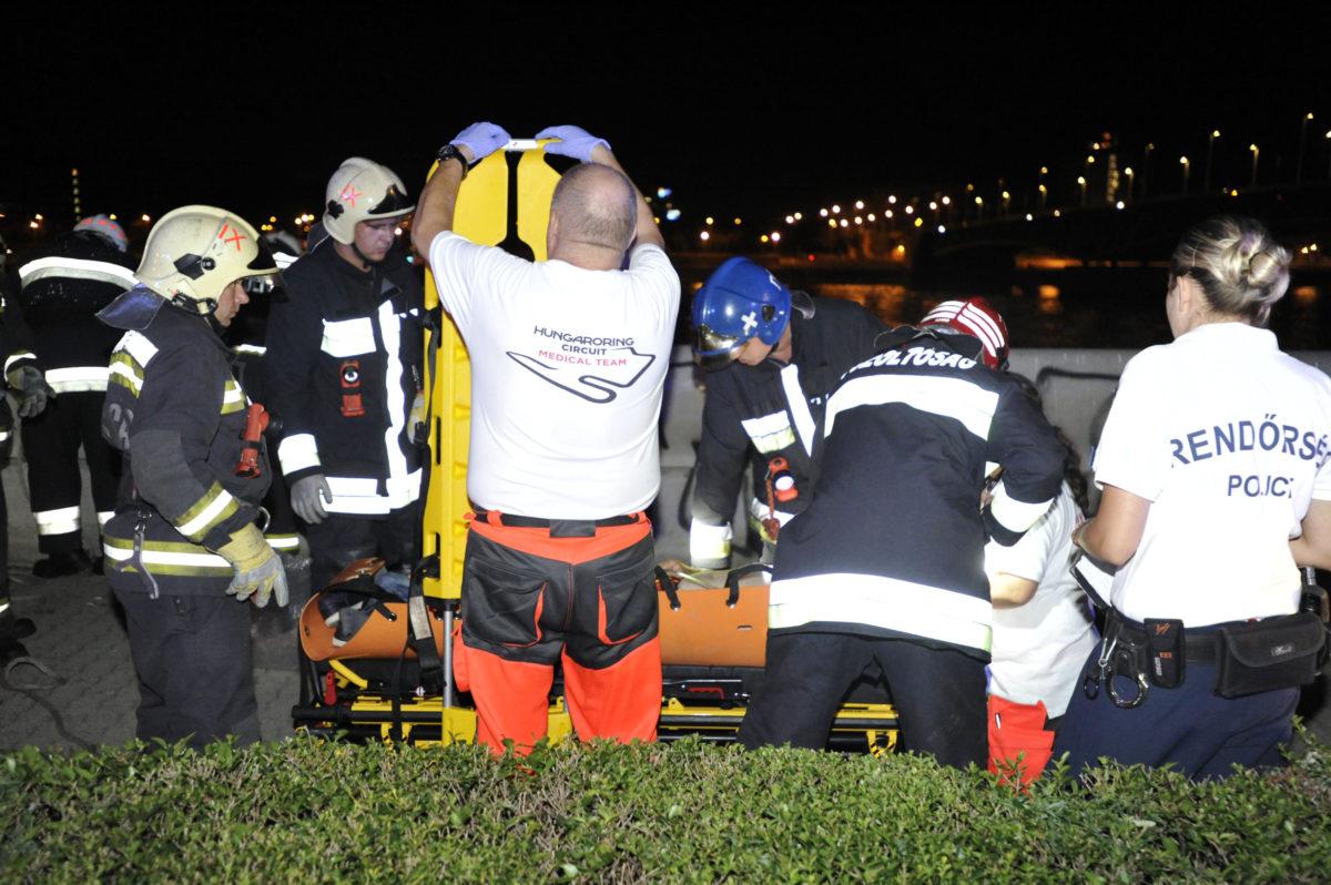 Tűzoltók és mentők speciális hordágyba fektetve mentenek egy férfit, aki a rakpartról a Duna-parti kövekre esett Budapesten, a Boráros térnél 2019. augusztus 8-án.