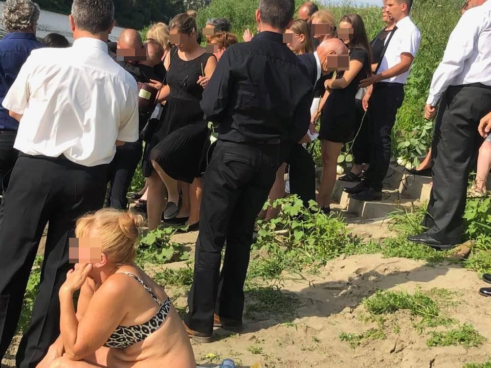 Gyászolók gyűrűjében napozik egy nő egy Tisza-parti halotti búcsúztatón.