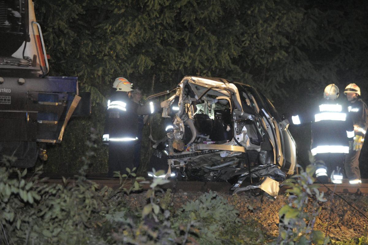 Tűzoltók egy összeroncsolódott személygépkocsinál, amelyben hárman meghaltak, amikor vonattal ütközött Kismarosnál 2019. augusztus 21-én.