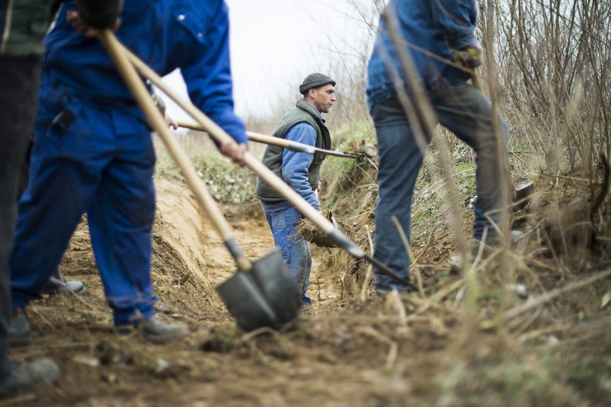A mezőgazdasági földutak karbantartására felvett közmunkások szikkasztó árkot ásnak Szakoly határában 2013. március 7-én.