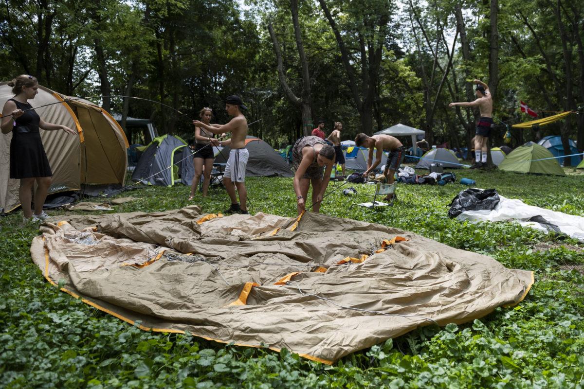 Fesztiválozók sátrat állítanak a 27. Sziget fesztivál helyszínén, az óbudai Hajógyári-szigeten 2019. augusztus 6-án.