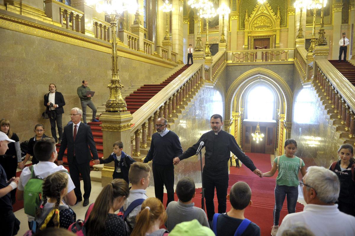 Hatszáz gyermek imádkozik a nemzetért, vezetőiért, a kereszténységért Soltész Miklóssal, a Miniszterelnökség egyházi és nemzetiségi kapcsolatokért felelős államtitkárával (b3) együtt az Országházban 2019. szeptember 21-én. Középen Csaba atya, mellette balra Sebastian atya.