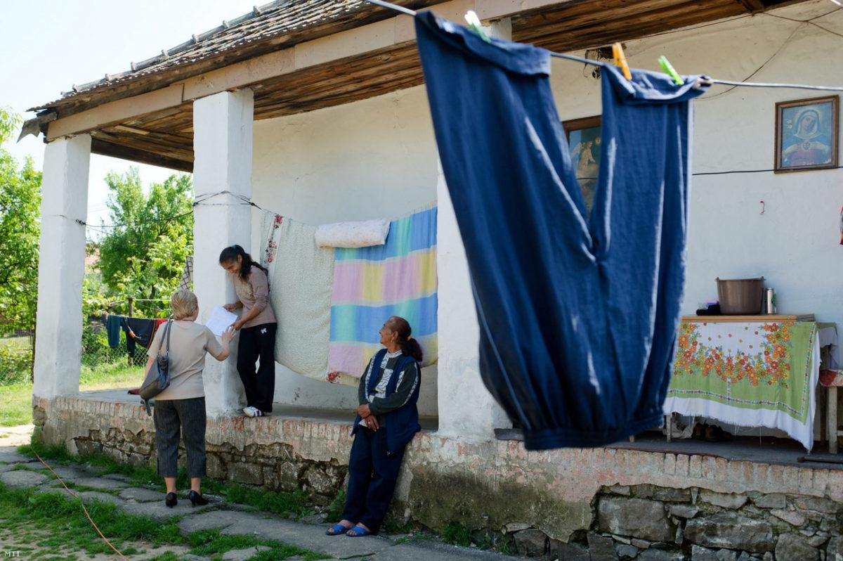 Lőrik Ágnes, a Szécsényi Gyerekesély Program tanodájának vezetője (b) nézi egy a program által támogatott fiatal lány füzetét a Nógrád megyei Nagylócon.