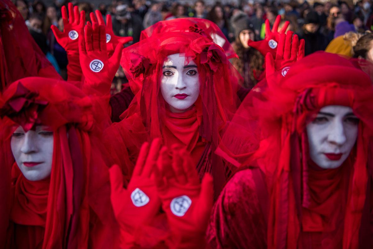 Az Extinction Rebellion környezetvédő szervezet piros ruhába öltözött aktivistái a negyedik globális klímasztrájkhoz kapcsolódó budapesti tüntetésen az Országház előtti Kossuth Lajos téren 2019. november 29-én.