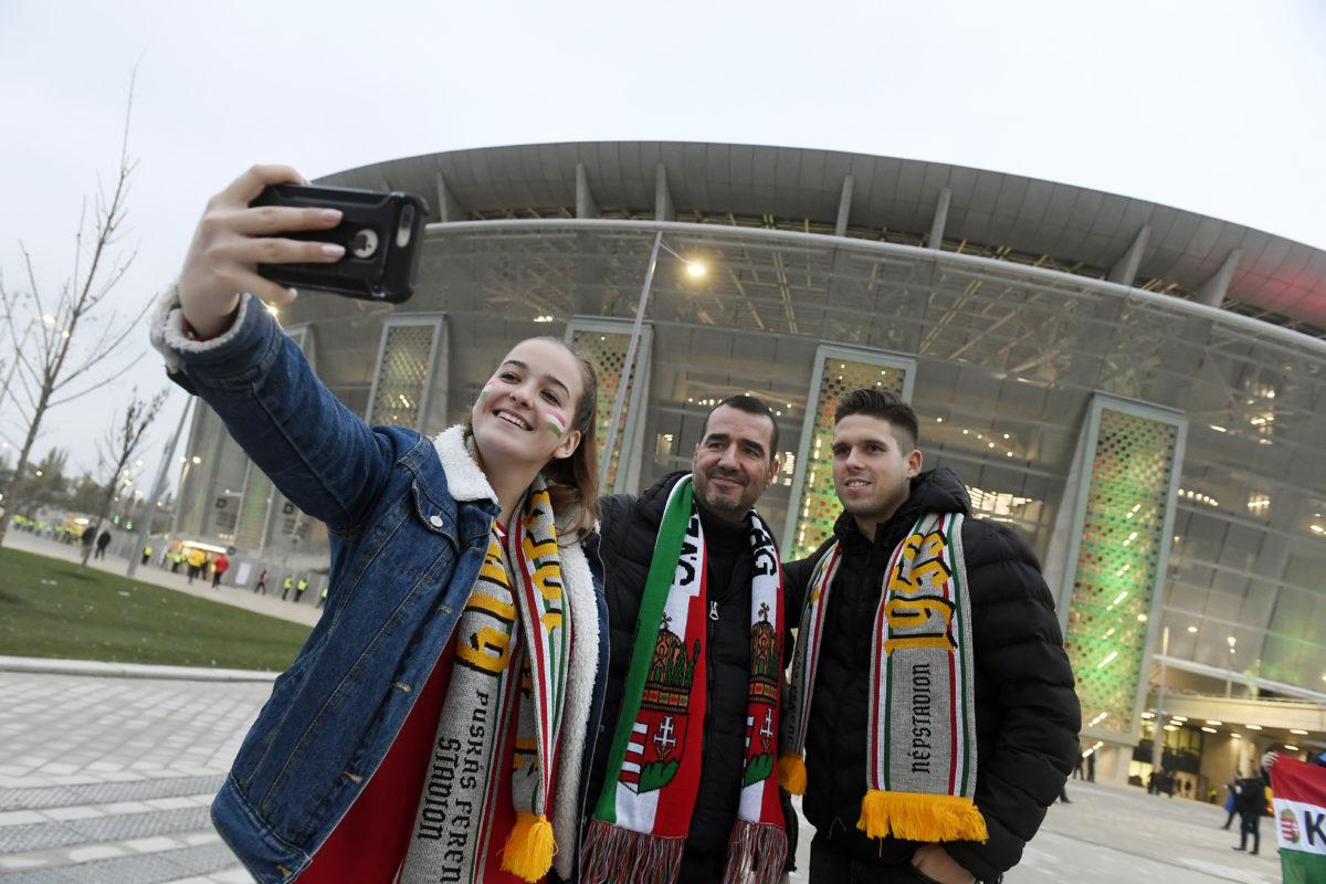 Szurkolók szelfit készítenek a Puskás Arénánál a stadion avatása előtt 2019. november 15-én.
