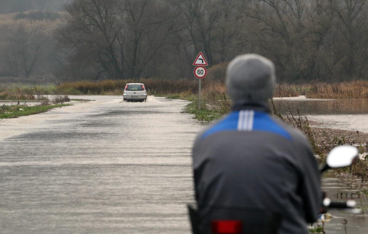 Személyautó gázol a vízben a Sajó folyó áradása miatt lezárt úton, Putnok és Sajóvelezd között 2019. november 14-én.