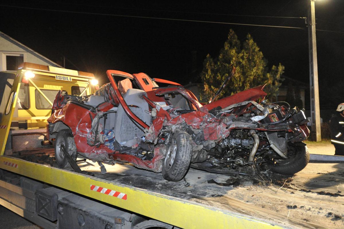 Elszállítanak egy összetört személygépkocsit, amely vonattal ütközött Vác külterületén, egy vasúti átjáróban 2019. november 17-én.