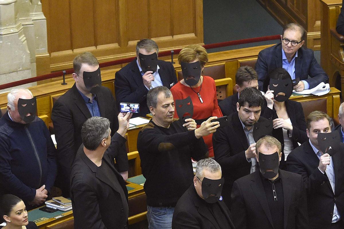 A DK, az MSZP és Párbeszéd képviselői a kulturális törvénycsomag szavazása közben tiltakozásul felállnak és fekete maszkot tartanak az arcuk elé az Országgyűlés plenáris ülésén 2019. december 11-én.