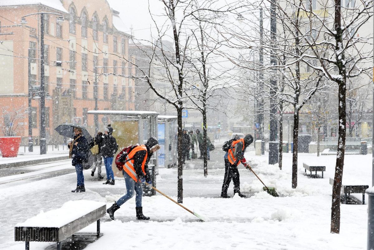 Havat lapátolnak a behavazott Móricz Zsigmond  körtéren, Budapesten 2019. december 2-án.
