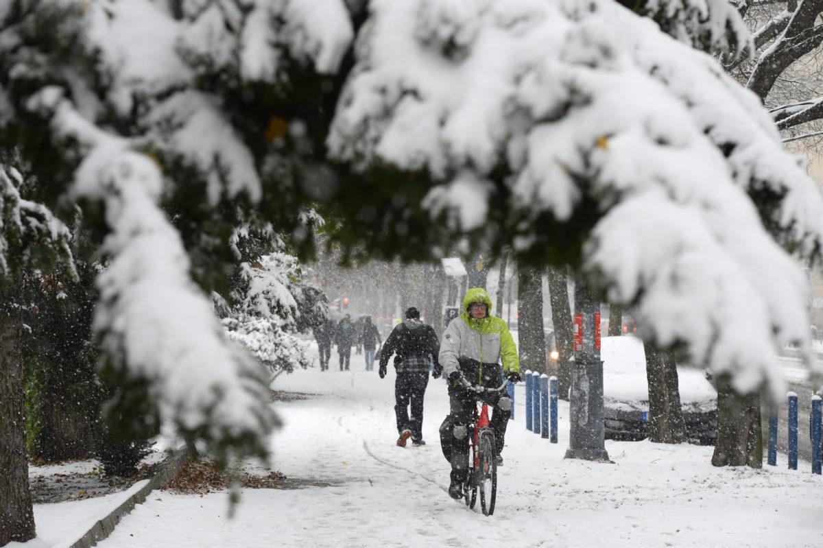 Egy férfi kerékpározik a behavazott XI. kerületi Bartók Béla úton 2019. december 2-án.