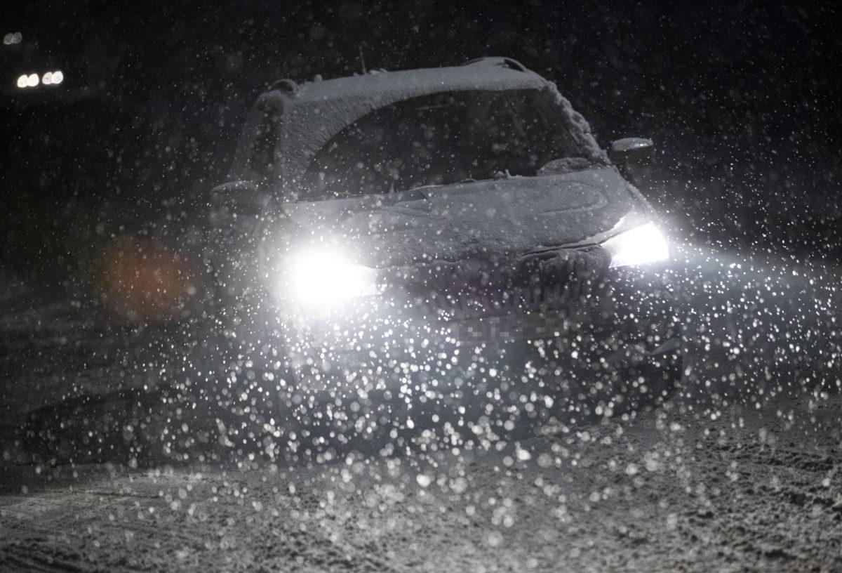 Személyautó halad a hóesésben Pócsmegyeren 2019. december 2-án.