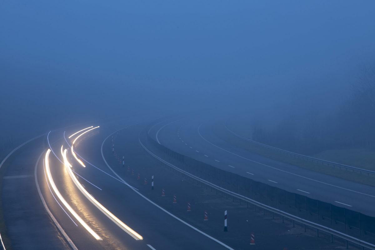 A hosszú expozíciós idővel készült felvételen az elhaladó járművek fényszóróinak fénye a sűrű ködben az M7-es autópályán Nagykanizsa közelében 2019. december 7-én.