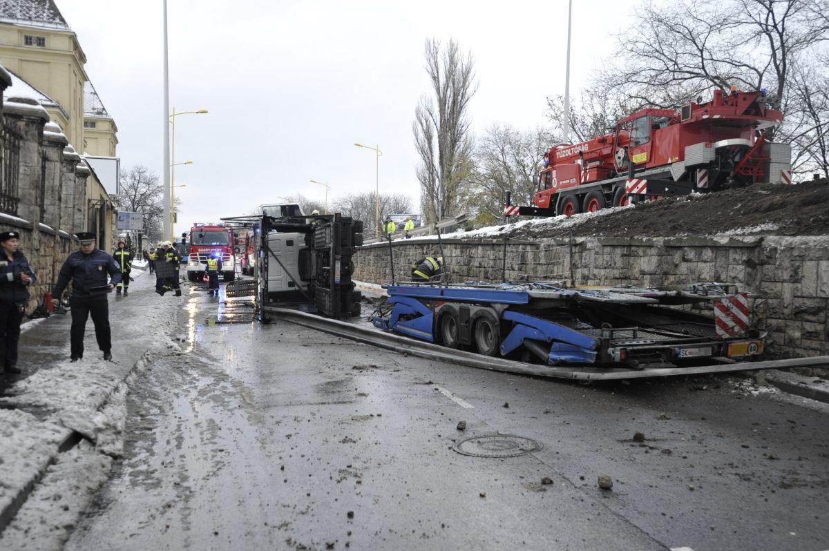 Tűzoltók és rendőrök a Budaörsi úton, ahova lezuhant egy tehergépkocsi a Nagyszőlős utcai felüljáróról 2019. december 2-án. A balesetben az autó vezetője megsérült.