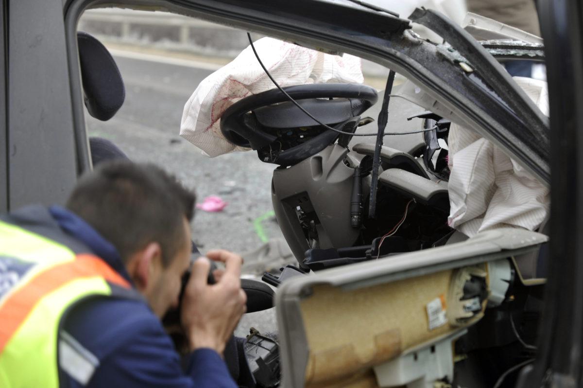 Rendőr helyszínel egy összeroncsolódott személyautó mellett a 6-os főúton, Ercsi közelében 2020. január 3-án.